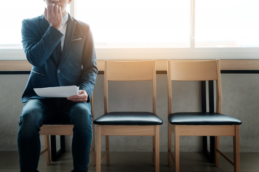Candidate Experience_young businessman in waiting room for job interview being anxious, on a row of chairs