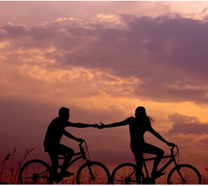 Silhouette of couple on bikes