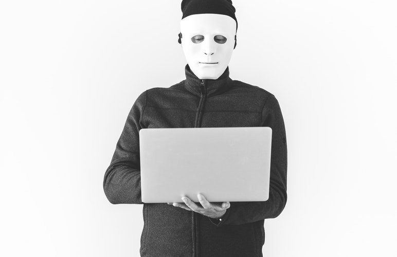 Man in mask on computer