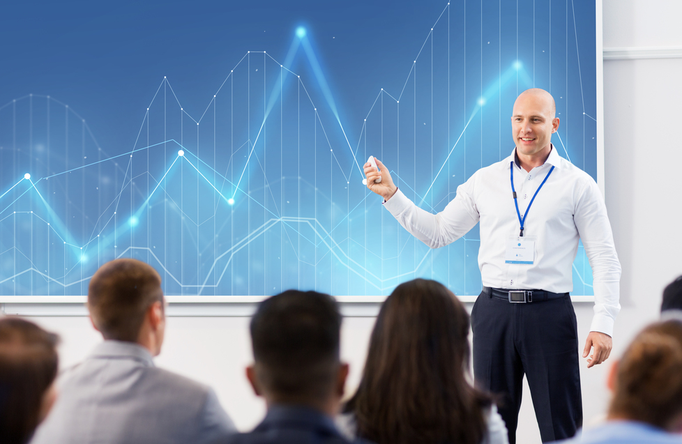 Driving Growth Through PA_smiling businessman or lecturer with diagram chart on projection screen and group of students at conference presentation or lecture. group of people at business conference or lecture