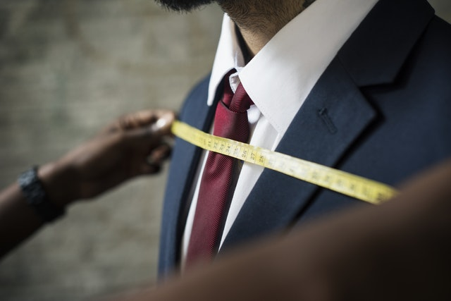 Employee Engagement Measuring_businessman in black suit with red tie being measured