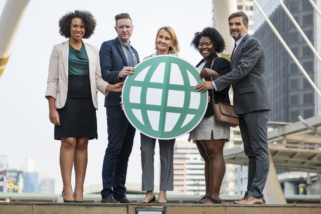 Expatriate Structures_Four diverse employees holding a teal globe symbol