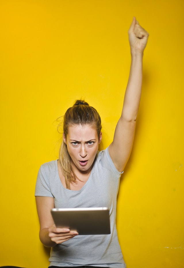 Extraordinary Achievement_woman holding tablet with excitement