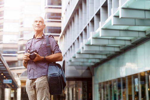 Gig Economy Could Go Extinct In CA_Senior man with camera in city