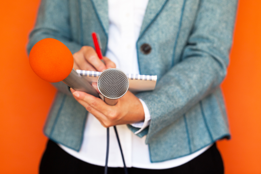 HR Articles_Best of October_woman in gray jacket with notepad and two microphones