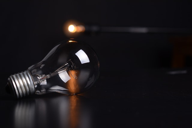 HR Do we Need It_Dimmed light bulb on a dark background