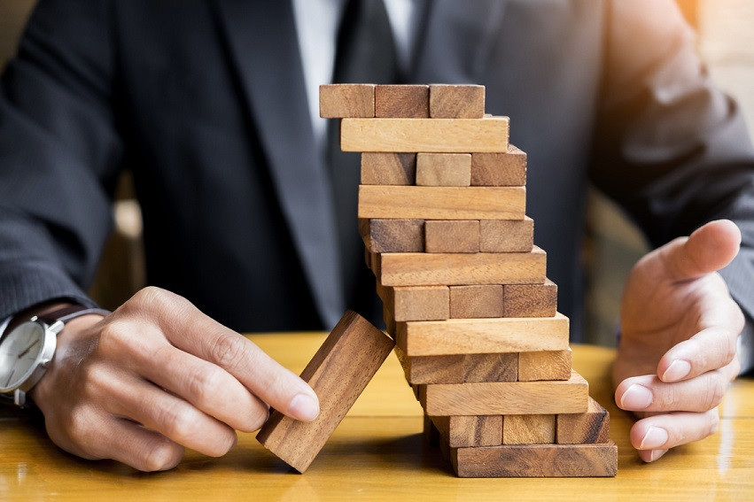 Microsoft makes HR changes_businessman and insurance gambling placing wooden block on a tower