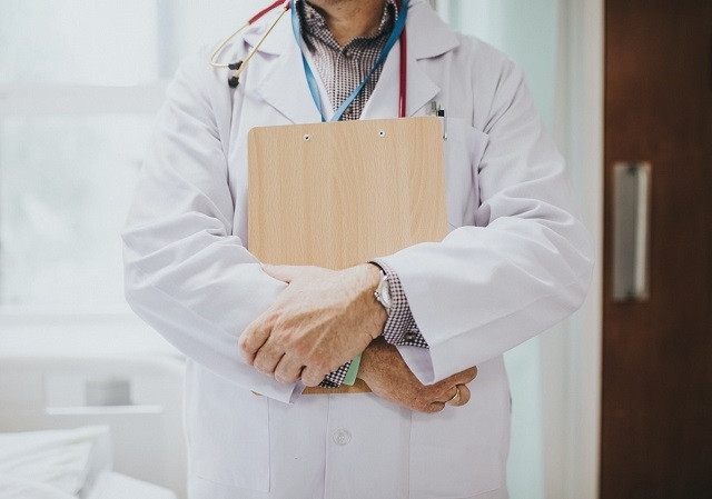 Physician-holding-clipboard-medical-information