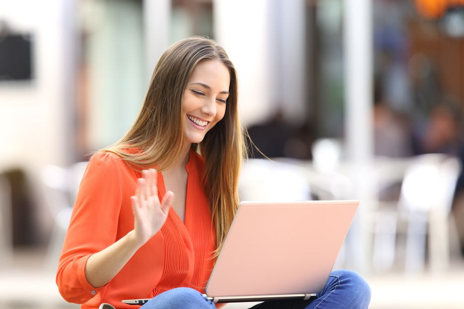 A girl waves to other attendees of a remote meeting.