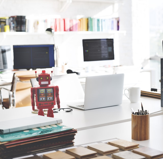 Social Media Recuiting Chatbot_office with red robot standing on a desk
