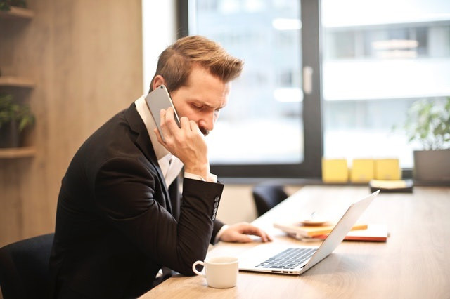 The HR Employee Burnout_man having a phone call in front of a laptop