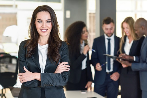 Training For Confidence_Businesswoman leader looking at camera in modern office with multi-ethnic business people working at the background