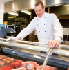 A butcher at a fresh meat counter in a grocery store with kitchen behind him