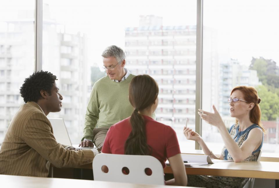 Co-workers sitting around table discussing culture change