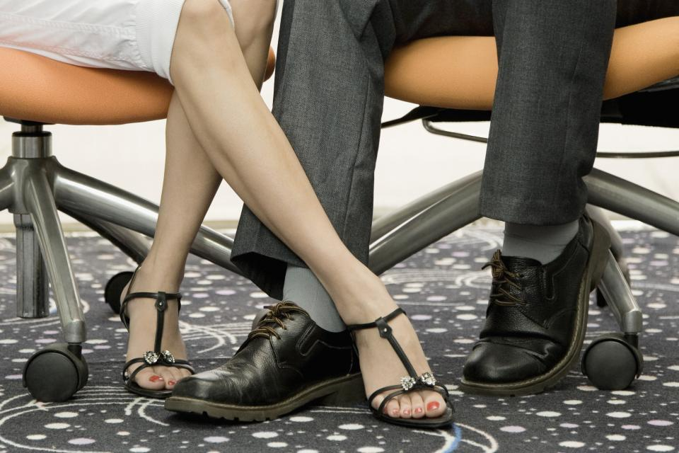 Female and male coworkers playing footsie