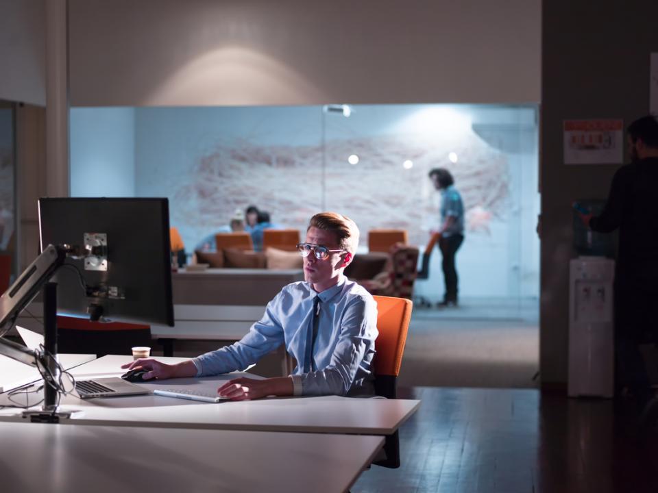 Người đàn ông trẻ tuổi làm việc trên máy tính vào ban đêm trong văn phòng tối