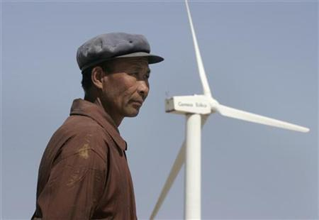 A man stands in front of a windmill at the Gansu Jieyuan Wind Power Company on the outskirts of Yumen