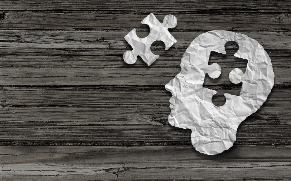 Paper head with missing puzzle piece on wood background