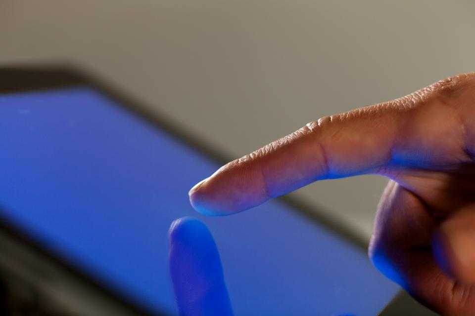 Finger touching tablet screen